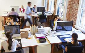 Wide Angle View Of Busy Design Office With Workers At Desks - open plan office
