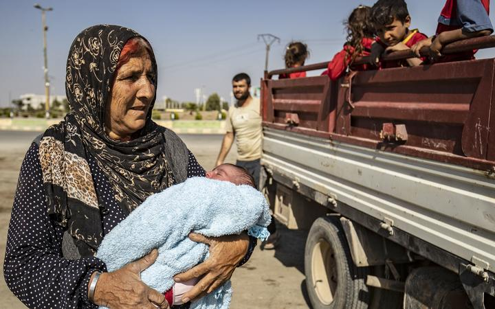Syrian Arab and Kurdish civilians arrive to Tall Tamr town, in the Syrian northwestern Hasakeh province, after fleeing Turkish bombardment on the northeastern towns along the Turkish border on October 10, 2019.