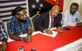 Mr Parkop signs the petition as Jeffrey Bomanak, Chairman of Free West Papua Movement (left) and James Yalya of NCD Governor's Regional Office (right) look on.