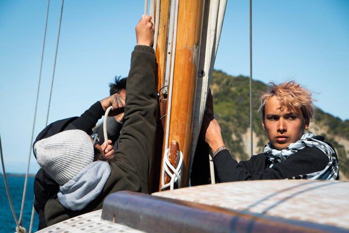 Crew members take instruction from their captain as they fasten the main sail.