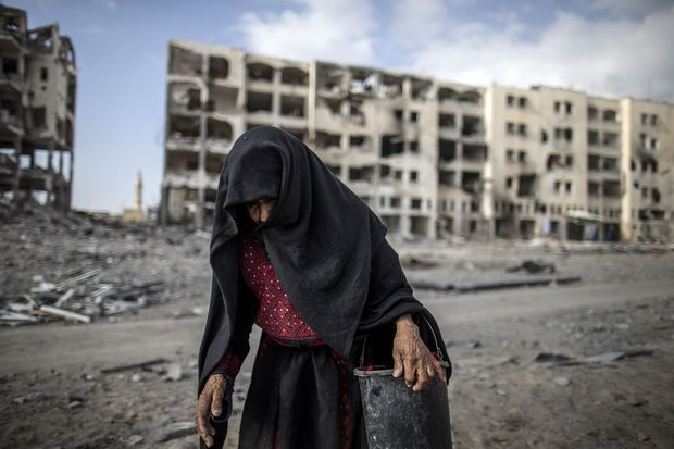 An elderly Palestinian woman carries a bucket walking past destroyed buildings in the Gaza Strip.