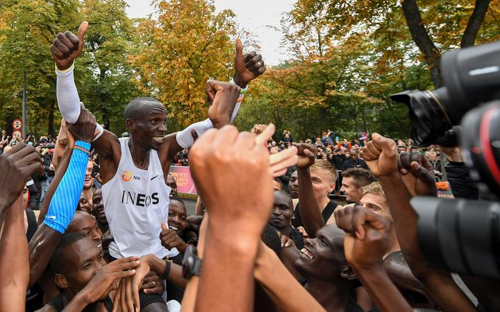 Eliud Kipchoge celebrates breaking the two hour barrier for a marathon distance with supporters and his team in Vienna.