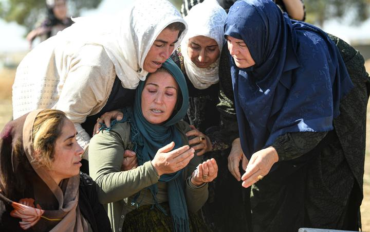 Relatives mourn in front of the grave of Halil Yagmur who was killed in a mortar attack a day earlier in Suruc near northern Syria border, during funeral ceremony in Suruc on October 12, 2019 .