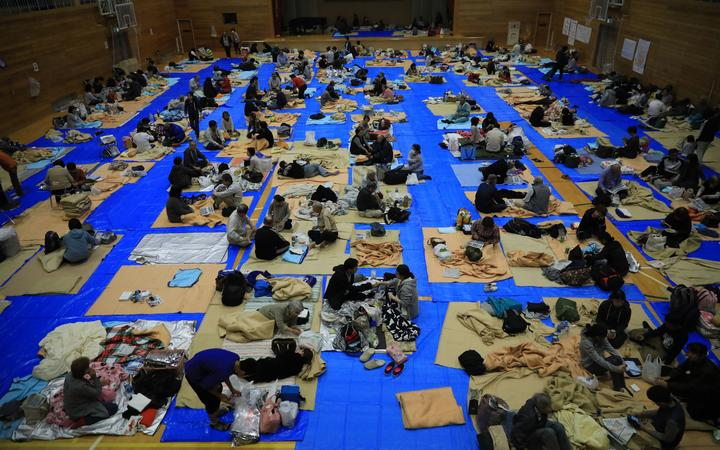 People stay at a shelter as the Chikuma River overflowed in Nagano City, Nagano prefecture on Oct. 13, 2019, one day after Typhoon No. 19, known as Typhoon Hagibis, a powerful super typhoon, made a landfall.