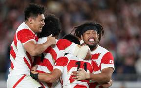 Japan rugby players celebrate their win over Scotland to qualify for RWC quarter-finals.