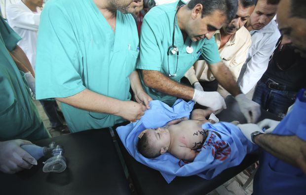 Palestinian medics treat an infant, who medics said was wounded in an Israeli air strike.