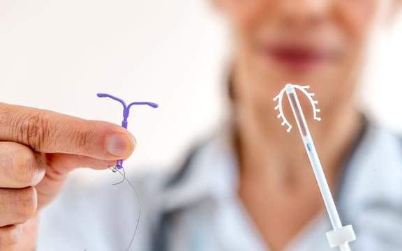 Female doctor holding two kinds of intrauterine device for birth control IUD