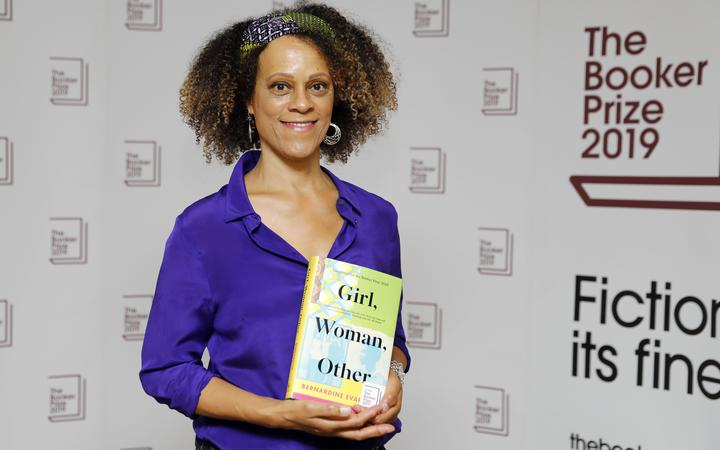 British author Bernardine Evaristo poses with her book 'Girl, Woman, Other' that won her the 2019 Booker Prize for Fiction