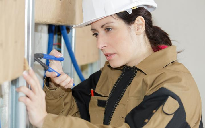 tradeswoman on site using pliers