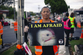 Leona Tavui holds a protest sign at an Auckland Save Movement Vigil outside Tegel in Henderson.