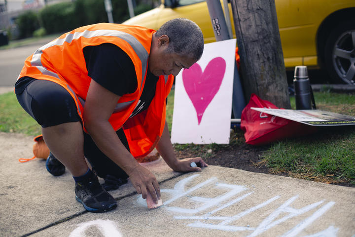 Leona Tavua, of the Auckland Save Movement, writes 'animal lives matter' on the pavement outside a Henderson slaughterhouse.
