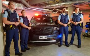 Police officers stand next to the new special patrol vehicle.