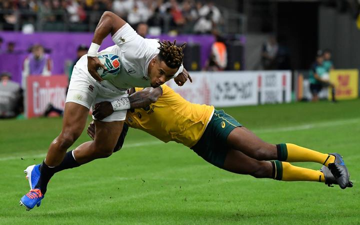 England's wing Anthony Watson (L) is tackled during the Japan 2019 Rugby World Cup quarter-final match between England and Australia at the Oita Stadium in Oita on October 19, 2019. (Photo by CHRISTOPHE SIMON / AFP)