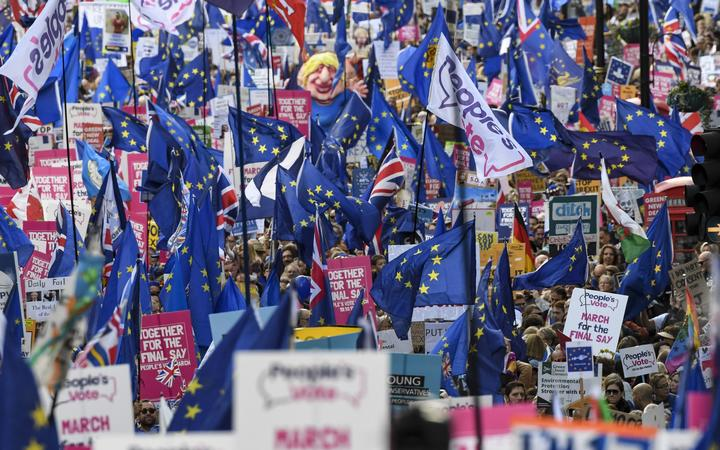 Demonstrators hold placards and EU and Union flags as they take part in a march by the People's Vote organisation in central London on October 19, 2019, calling for a final say in a second referendum on Brexit.