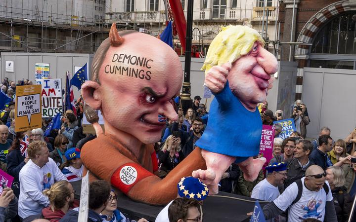 Demonstrators march with an effigy depicting Britain's Prime Minister Boris Johnson as a puppet operated by his advisor Dominic Cummings during a rally by the People's Vote organisation in central London on October 19, 2019,