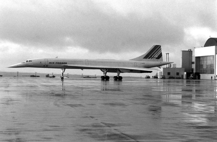 A left side view of an Air France Concorde supersonic passenger aircraft parked on the flight line during a stopover at the air station.