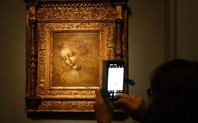 "A person take a picture of  an oil on wood painting by Leonardo da Vinci's  "" The Head of a Woman—also known as La Scapigliata "","