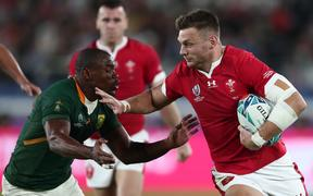 South Africa's wing Makazole Mapimpi (L) tackles Wales' first five Dan Biggar during the Japan 2019 Rugby World Cup semi-final match between Wales and South Africa.