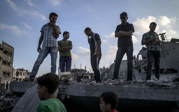 Palestinians stand on top of a destroyed building in the devastated area of Shejaiya in Gaza City.