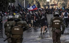 Demonstrators clash with riot police in Santiago, Chile, during protests against the government's economic policies