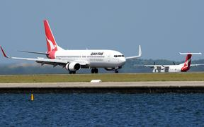 A Qantas Boeing 737, left,lands as a Qantas Q-400, right, prepares to take off at Sydney International Airport in November 2011.