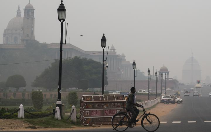 A man rides a bicycle along a street under heavy smog in New Delhi on October 29, 2019. (Photo by Jewel SAMAD / AFP)