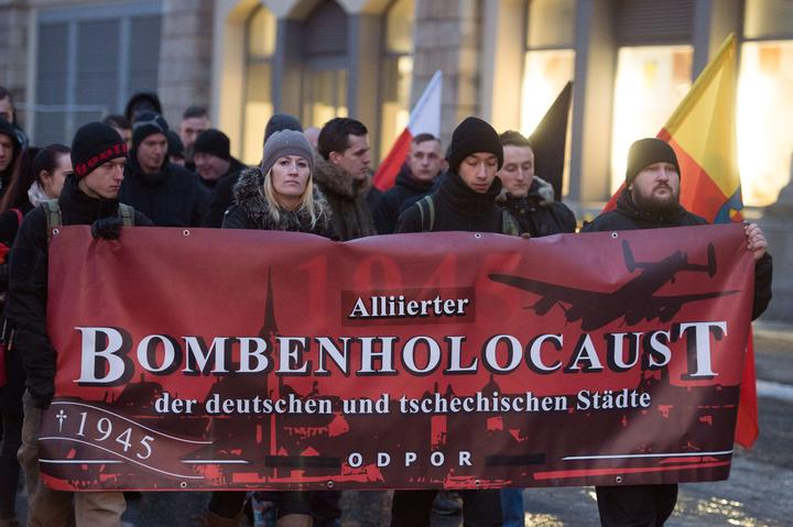 Right-wing extremists hold up a banner reading 'Alliierter Bombenholocaust' (lit. 'Allied Bombing Holocaust') during a so-called funeral march in Dresden on 11 February 2017.