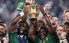 South Africa's Siya Kolisi lifts the Webb Ellis Trophy with Cyril Ramaphosa.
