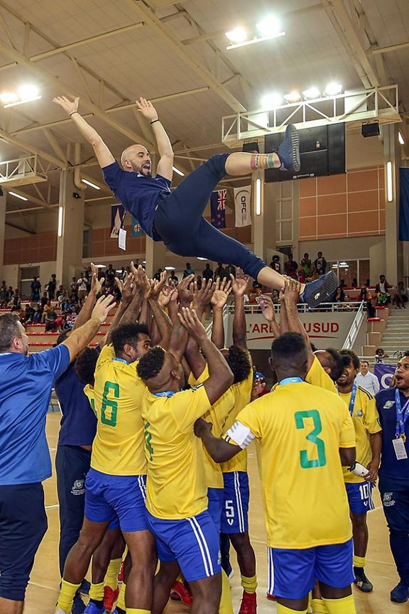 Solomon Islands players throw coach Vinicius Leite into the air in celebration.