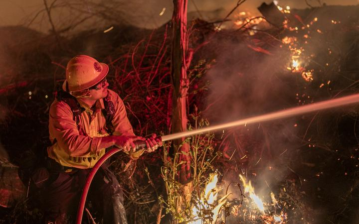 A firefighter at the Maria Fire, which exploded to 8000 acres on its first night, on 1 November 2019 near Somis, California.