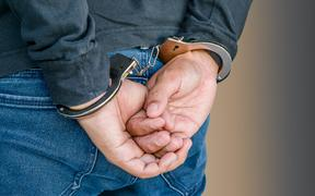 Male hands locked in handcuffs on white, With Clipping Path.