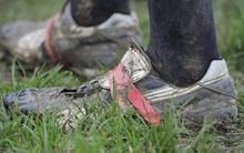 Detail of mud covered rugby boots held together with red tape, player standing in grass.