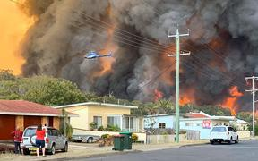 Flames from an out of control bushfire seen from a nearby residential area in Harrington, some 335km northeast of Sydney.