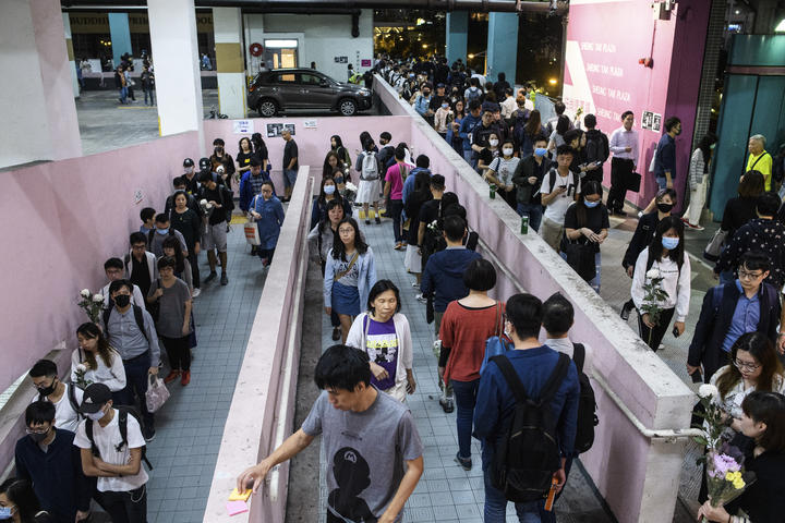 Mourners queue to pay their respects at the car park where student Alex Chow, 22, fell during a recent protest in the Tseung Kwan O area on the Kowloon side of Hong Kong on November 8, 2019.