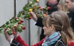 People place roses at a portion of the wall at Bernauer Strasse during a commemoration ceremony for the 30th anniversary of the fall of the Berlin Wall, at the Berlin Wall Memorial, Bernauer Strasse in Berlin.