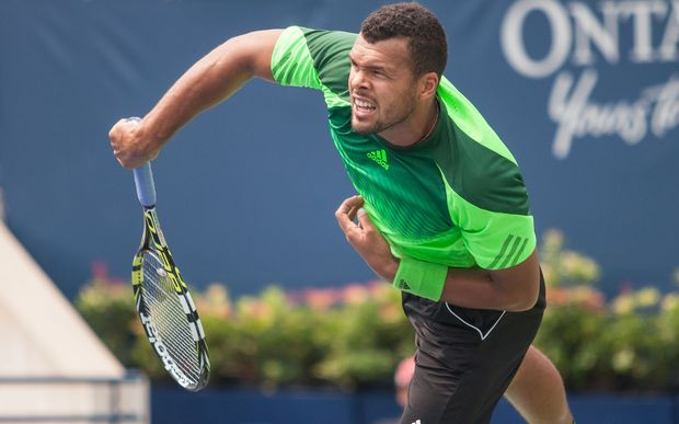 Jo-Wilfried Tsonga (FRA) returns the ball during his match against Novak Djokovic (SRB) at the 2014 Rogers Cup being played in Toronto.
