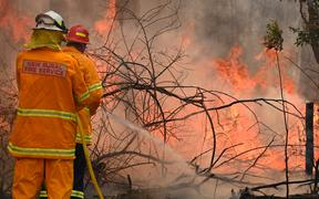 Firefighters tackle a bushfire to save a home in Taree, 350km north of Sydney on 9 November 2019.