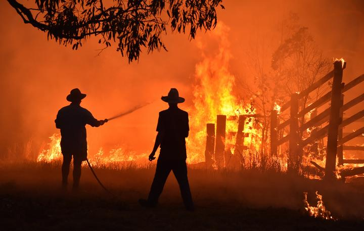Residents defend a property from a bushfire at Hillsville near Taree, 350km north of Sydney on November 12, 2019