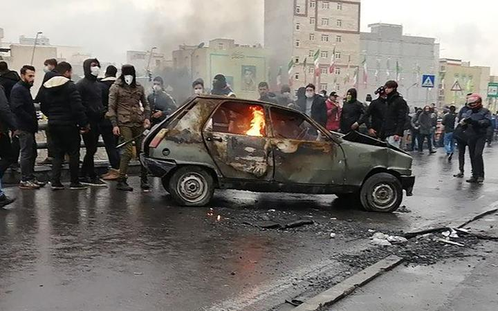 Iranian protesters gather around a burning car during a demonstration against an increase in gasoline prices in the capital Tehran, on November 16, 2019. -