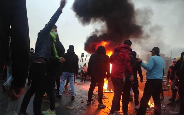 Iranian protesters gather around a fire during a demonstration against an increase in gasoline prices in the capital Tehran, on November 16, 2019.