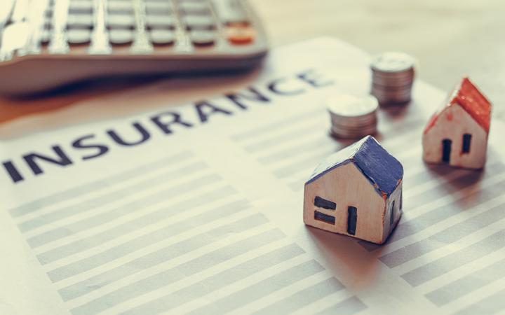 Home insurance form with money, calculator and models of houses.
