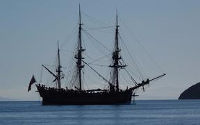 A big three masted sailing ship in the bay.