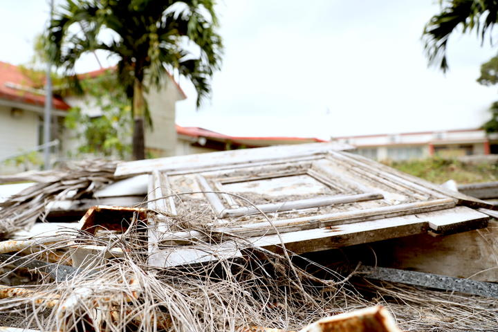 Tonga's Parliament was severely damaged by Cyclone Gita in 2018. Panels of wood, metal poles, and concrete are still scattered around the site.