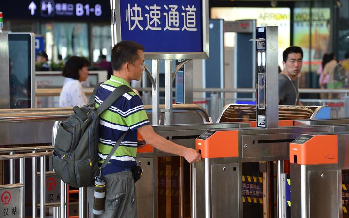 A passenger scans his face after having his train ticket automatically scanned for check-in at the Wuhan Railway Station in Wuhan city, central China's Hubei province, 21 August 2017.