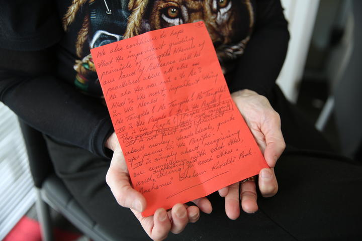 Hans Dalton's mother, Christine Wilson, holds a letter she wrote at the seventh anniversary of her son's death.
