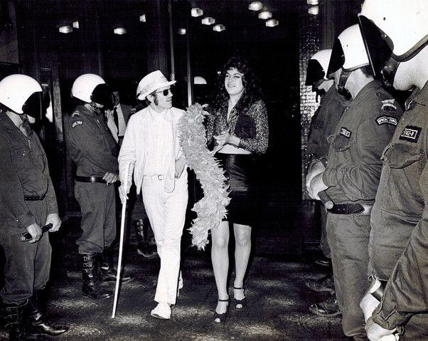 Neville Purvis and Cousin Cheryl - Arthur Baysting and Jean Clarkson - walk the police gauntlet to attend the premiere of 'Sleeping Dogs' at the Auckland Civic, 6 October 1977.