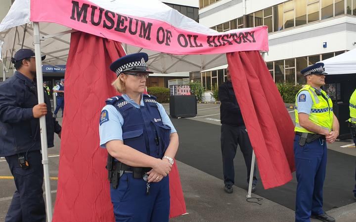 Police stand guard as OMV security dismantles the protesters' construction at the oil company's offices in New Plymouth.