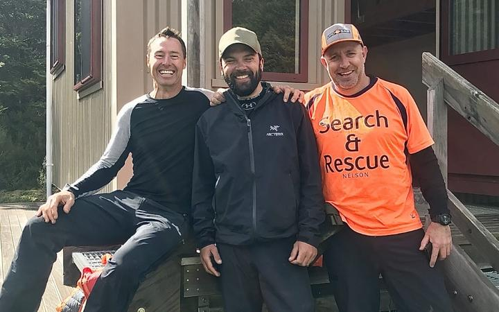 US hiker Chris Muse, centre, with LandSAR volunteers Dwayne Lohmann, left, and Kris Monopoli, right, who rescued him after he was swept down a flooded tributary near the Motueka River.