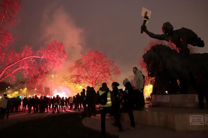"Protestors gather near the ""Triomphe de la Republique"" statue among flares during a demonstration against the pension overhauls, in Paris, on December 5, 2019 as part of a nationwide strike."