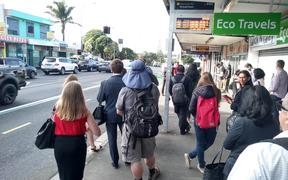 Commuters wait at Mt Roskill shops for a replacement bus supposed to arrive every 15 minutes - many people had been waiting longer.